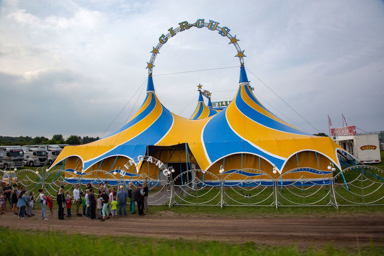 Circus Amusement Park Architecture Arts Culture And Entertainment Building Exterior Built Structure Cloud - Sky Crowd Day Group Of People Incidental People Large Group Of People Leisure Activity Men Nature Outdoors Real People Sky Travel Destinations Yellow