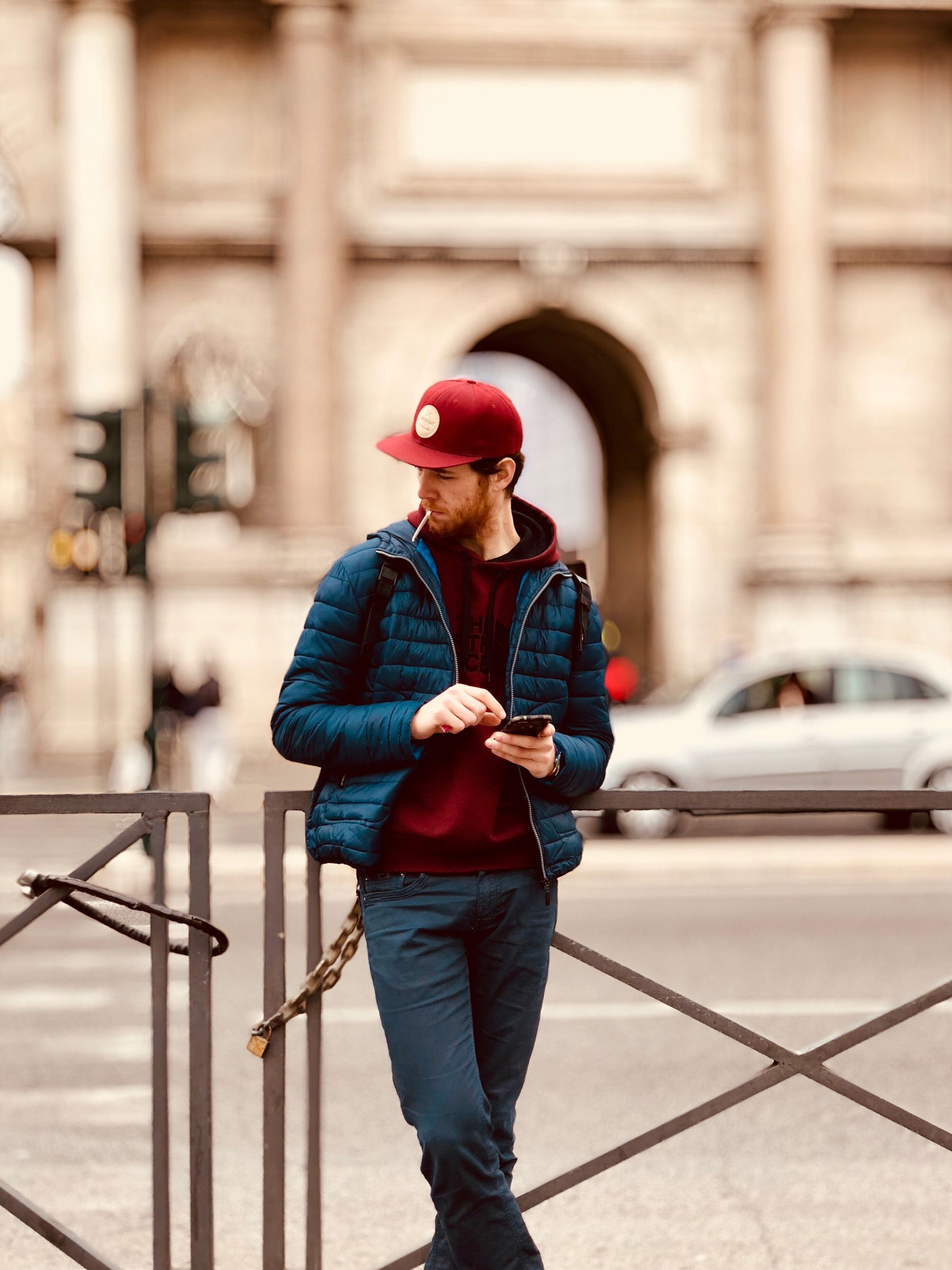 standing, one person, architecture, real people, city, built structure, lifestyles, young adult, building exterior, focus on foreground, transportation, connection, front view, day, clothing, mode of transportation, full length, mid adult, car, outdoors