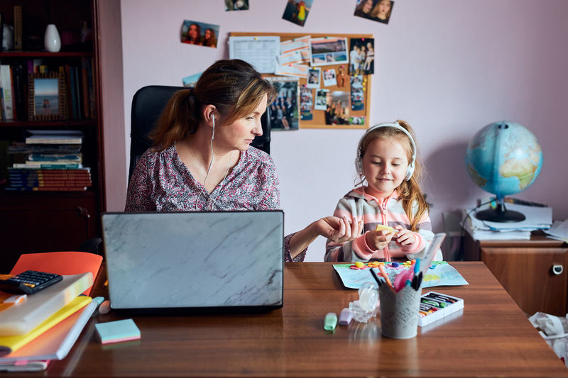Mother using laptop while sitting at home with daughter