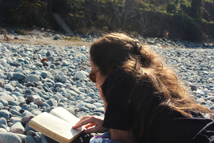 Young woman reading book on the beach, sun and summer holidays in black sea