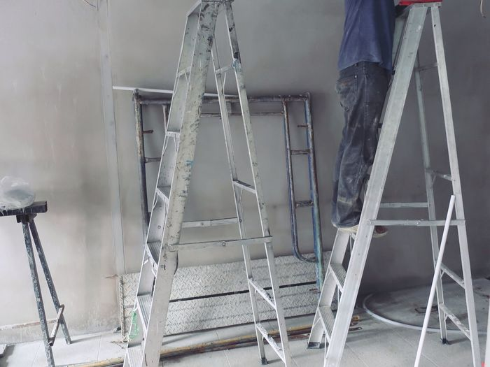 Low section of worker standing on step ladder at construction site