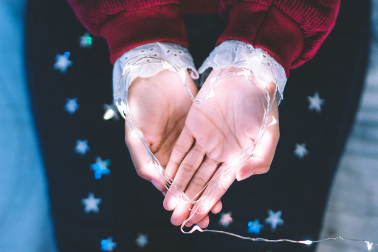 Cropped hands of woman holding illuminated string lights