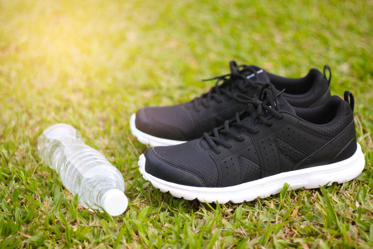 Close-up of shoes and water bottle on grass