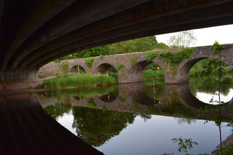 Reflection of bridge on water against sky