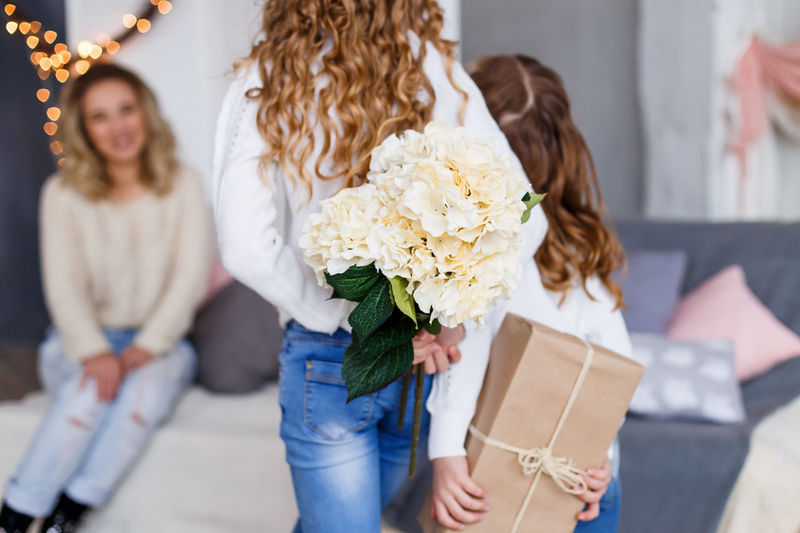 Daughters giving their mother a present and flowers Birthday Celebration Concept Congratulations Daughters Family Gift Happiness Happy Holiday Joy Love Mother Mother's Day Parenting Present