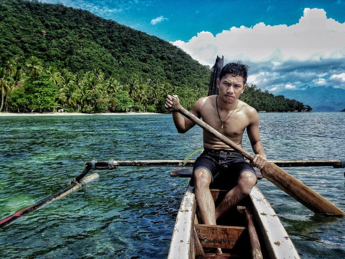 Shirtless man rowing outrigger boat in sea