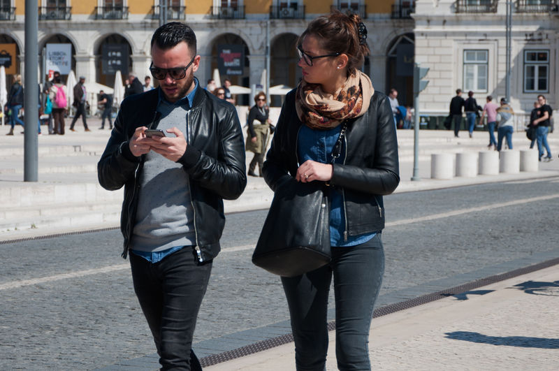 Couples. Architecture Building Exterior City Day Lisbon Mobile Phone Outdoors Portugal Praça Do Comércio Real People Technology Tourists Two People Wireless Technology Young Adult