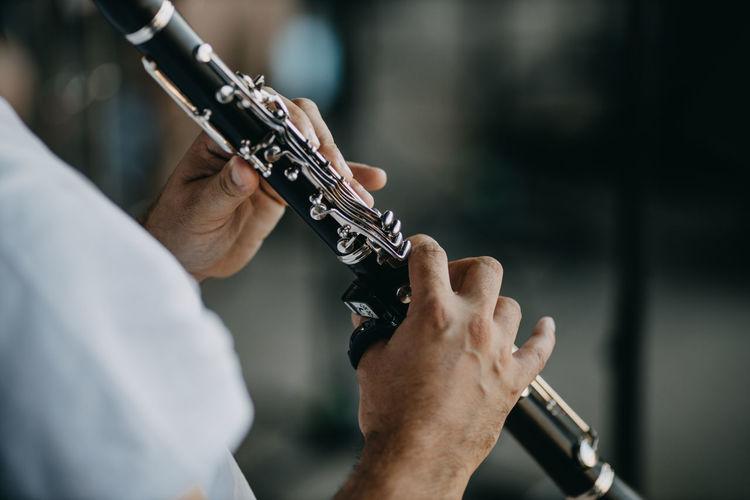 Close up man playing clarinet