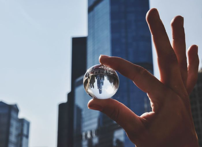 Close-up of hand holding crystal ball against skyline