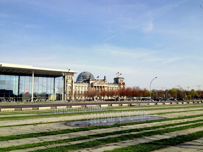 Fountain By Bundestag Against Sky In City