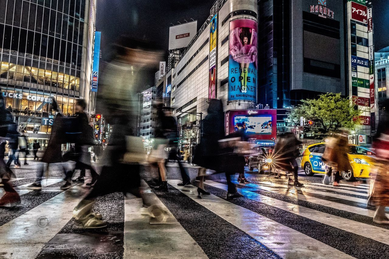 BLURRED MOTION OF PEOPLE WALKING ON CITY STREET BY BUILDINGS