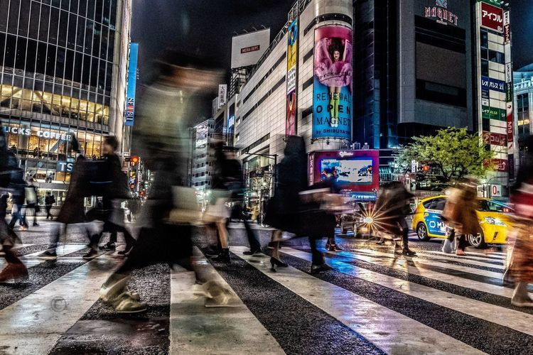 Blurred motion of people walking on city street at night
