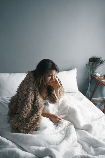 High angle view of woman drinking lemon tea sitting on bed