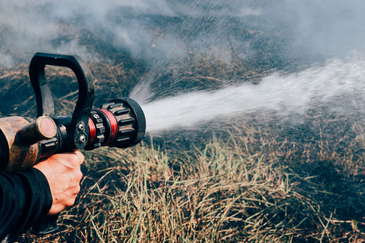Cropped hand spraying water in burning forest