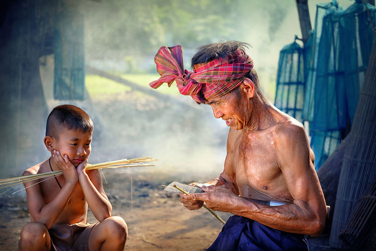 Senior Man With Grandson In Village