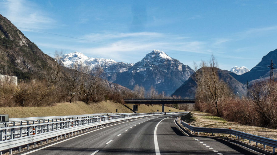 Mountain Transportation Road Snow Cold Temperature Mountain Range The Way Forward Winter Beauty In Nature Scenics - Nature Direction Sky No People Nature Snowcapped Mountain Cloud - Sky Sign Day Road Marking Diminishing Perspective Crash Barrier Outdoors Dividing Line