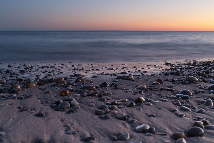 Surface level view of sea shore at sunset