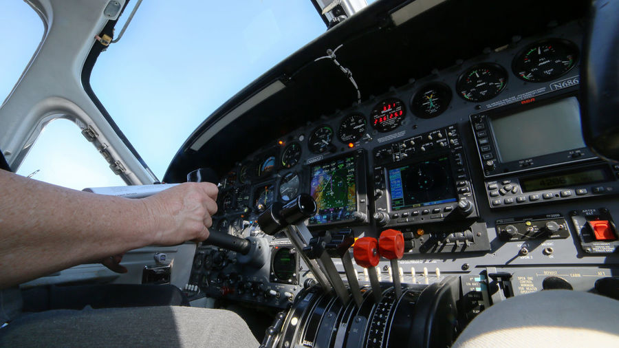 Cropped Image Of Hand Controlling Cockpit In Airplane