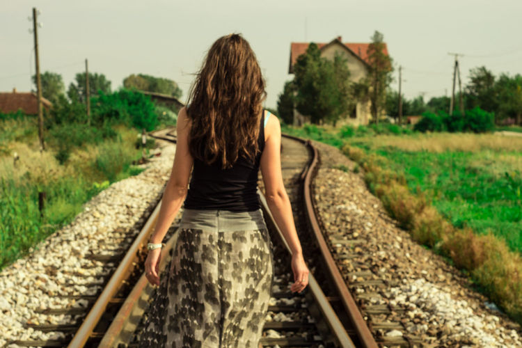 Woman standing on railroad track
