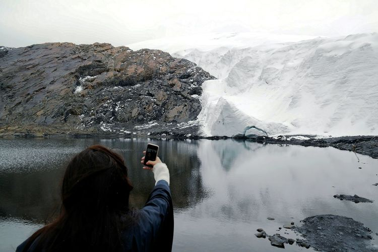 Rear view of woman photographing in lake against sky