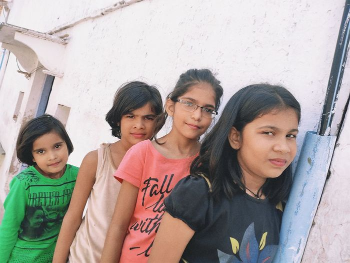 Portrait of siblings standing against wall