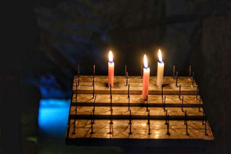 inside a CAVE Illuminated Flame Heat - Temperature Burning Candle Glowing Close-up Candlestick Holder Candlelight Darkroom