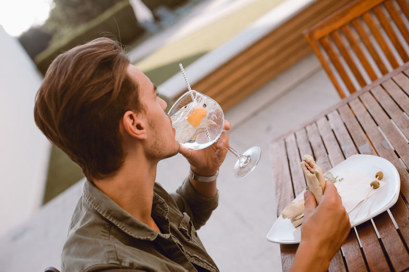 High angle view of woman drinking glass on table