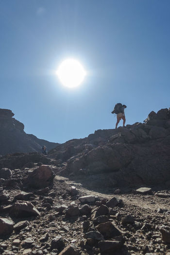 Hiker walking up rocky hill with sun shining bright Adventure Arid Climate Backpack Beauty In Nature Exploration Explore Hike Hiker Hiking Leisure Activity Mountain Mountain Range Nature Nature One Person Outdoor Outdoor Photography Outdoors Rugged Scenics Summer Sun Sunlight Wild Wilderness