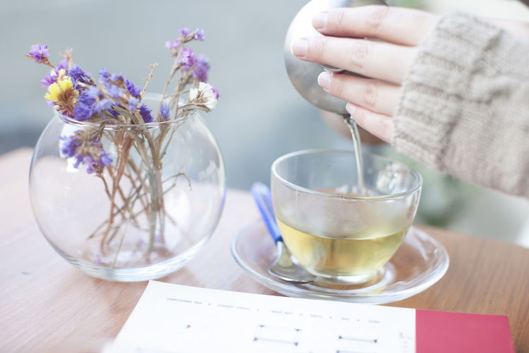 Cropped image of woman pouring tea in cup from kettle at cafe