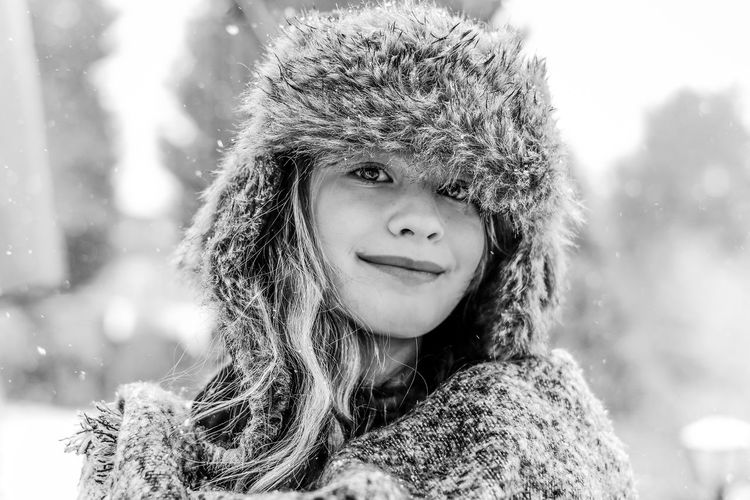 Portrait of smiling girl wearing fur hat during winter