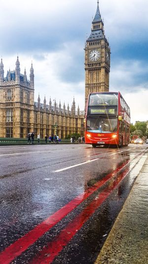 Double-decker bus on city street by big ben against sky