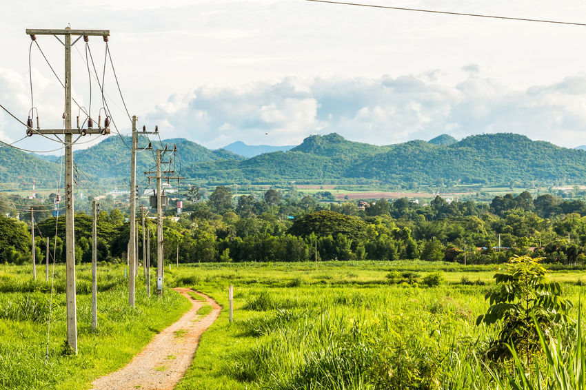 Local road beside low voltage pole. Beauty In Nature Cable Cloud - Sky Connection Day Electricity  Electricity Pylon Field Grass Landscape Mountain Mountain Range Nature No People Outdoors Poles; Road; Scenics Sky Sunny; Terrain; Transportation Tropical; White Cloud;