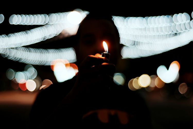 Close-Up Of Man Igniting Cigarette Lighter At Night