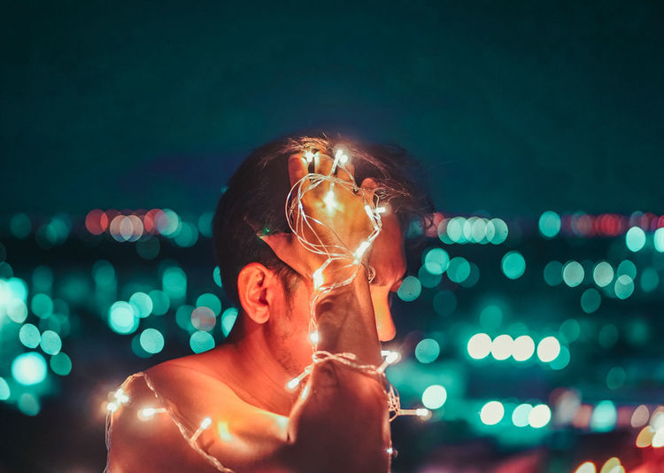 Portrait of young man holding illuminated light painting at night