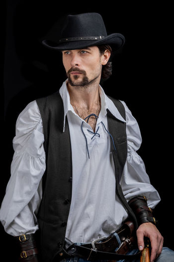 Handsome young man. This is an American cowboy. A vow to a white shirt, brown waistcoat and blue jeans. Black shoes on the feet. Carries a shtyapa, on a belt two pistols. The hair is of medium length; on the face is a beard and mustache. Authentic photo. Culture of America. Cowboy Wild West America American Gun National Authentic Moments Lifestyles Lifestyle One Person Candid Authentic Hat Clothing Front View Men Black Background Standing Real People Males  Young Men Well-dressed Beard Adult Contemplation