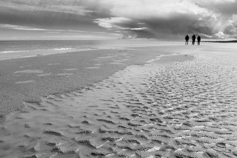 Storm cloud Beach Walking At Low Tide Calm Before The Storm Friendship On Coast Low Tide And Three People Together Nova Scotia, Canada Sand Ripples Storm Clouds Are Brewing Black And White Beach Scene Shoreline Beach