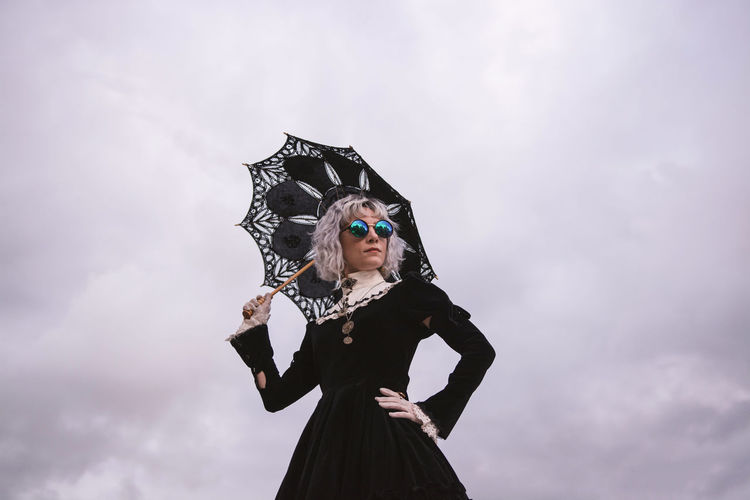 Low angle view of woman holding umbrella while standing against cloudy sky