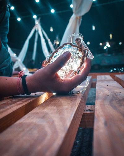 Midsection of woman holding illuminated jar over table outdoors