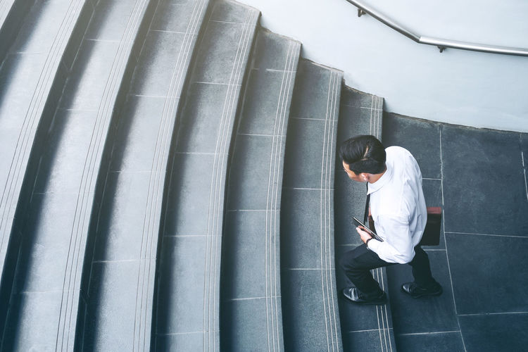 High angle view of businessman climbing on steps