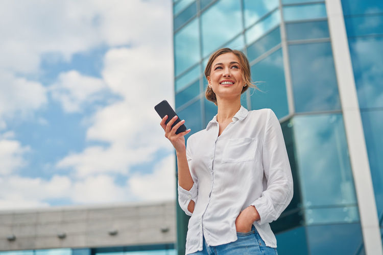 Close-up of smiling businesswoman standing by glass outdoors