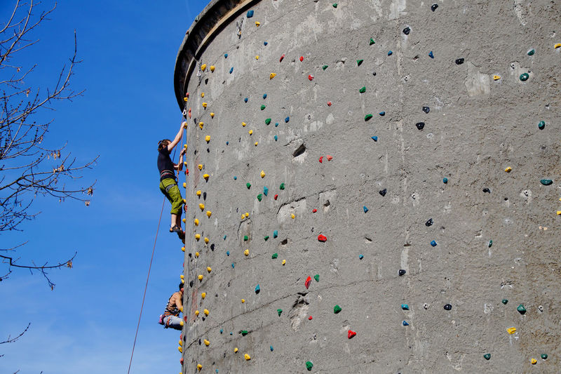 Low Angle View Of Man And Woman Climbing On Wall Against Sky
