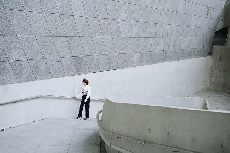 Rear view of woman walking on concrete wall