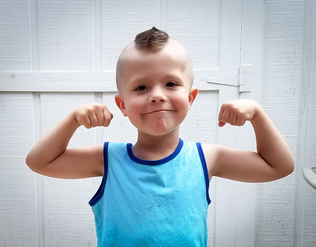 Portrait of cute boy with a double biceps pose