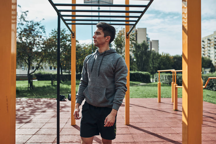 Young man bodybuilder having break during his workout in a modern calisthenics street workout park