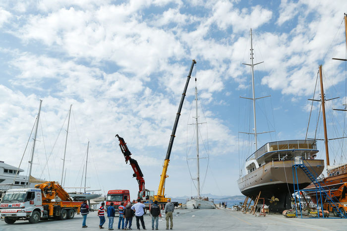 Shot taken on the 6th of April, 2017 at the yacht marine in Bodrum. Workers are installing a mast using a craine on a newly built luxury motor sailing yacht Rhea, which is built in Bodrum, Turkey Backgrounds Bodrum Crane High Install Installing Luxury Luxurylifestyle  Marine Mast People Sailing Sails Sea Port Ship Ship Building Shipyard Sky Tower Turkey Vessel Work Yacht Yachting Yachts