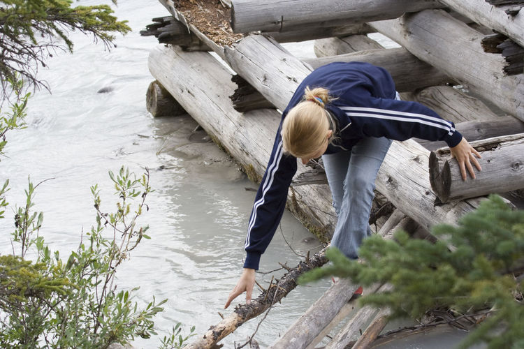 High angle view of woman walking on wooden raft at river