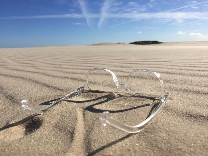 Surface Level View Of Clear Glasses On A Sandy Beach
