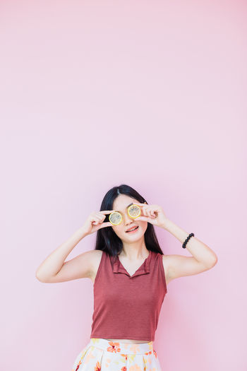 Portrait of young woman looking through lemon slices against pink background