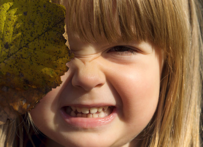 Close-up portrait of cute girl holding leaf