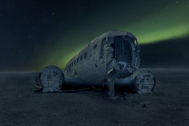 Abandoned airplane on land against sky at night